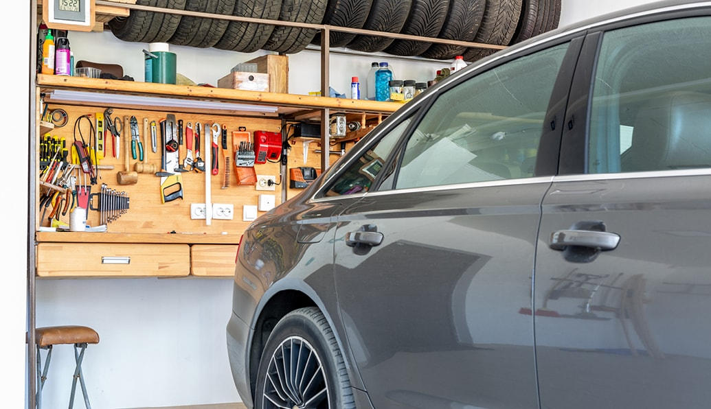 A car parked in a garage with a wall full of organized equipment behind it.