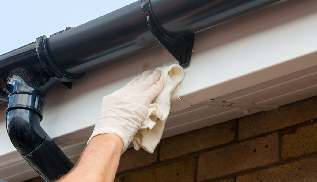 A gloved craftsman repairs trim under a gutter pipe.