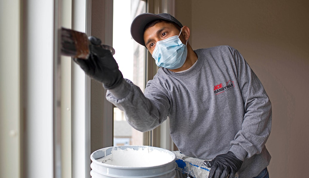 A craftsman in protective gear paints the trim on a window.
