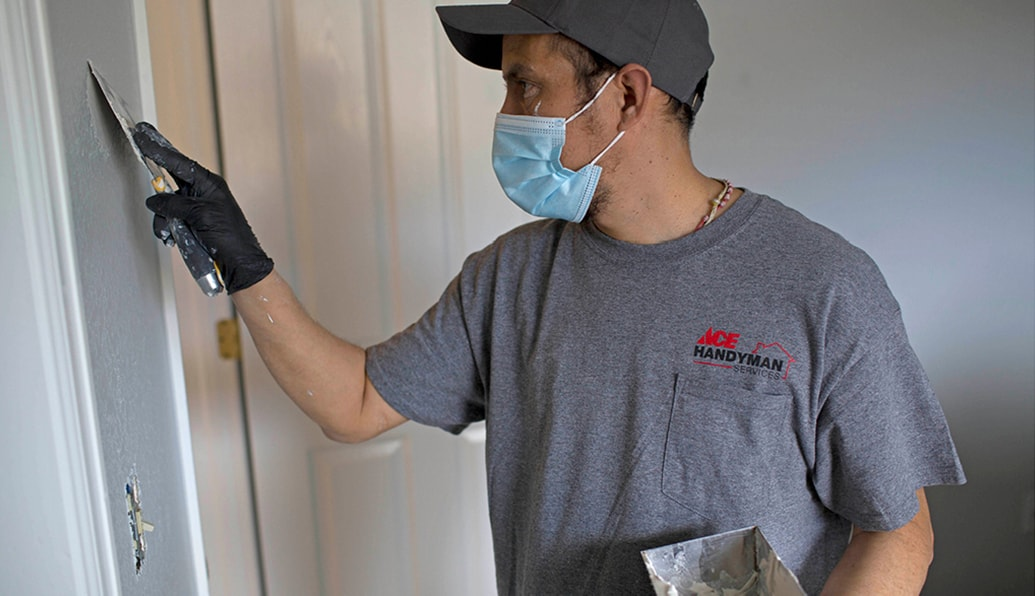 A craftsman in protective gear uses a trowel.