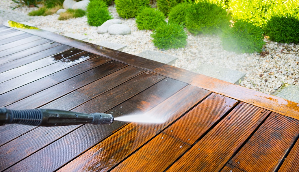 A power washer is cleaning the grime off a deck.