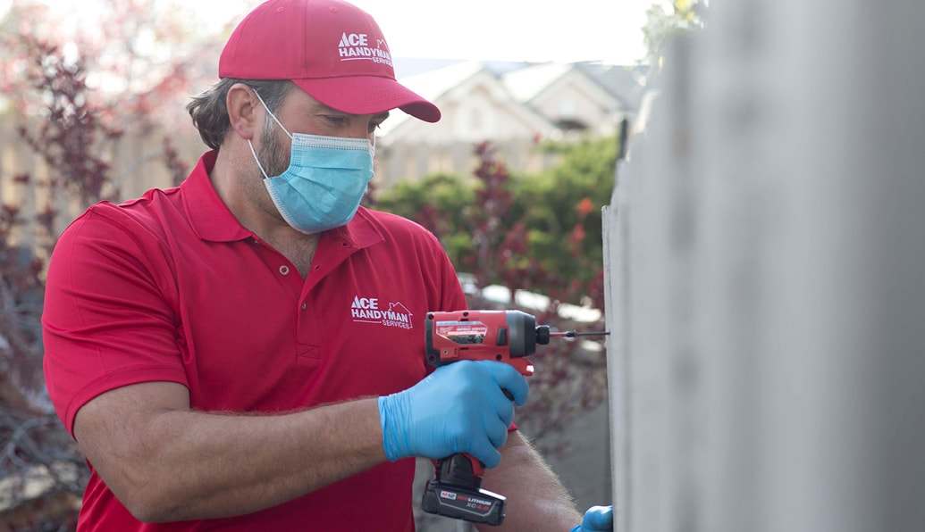 An outdoor photo of a uniformed Ace craftsman repairing a fence with a power screwdriver.
